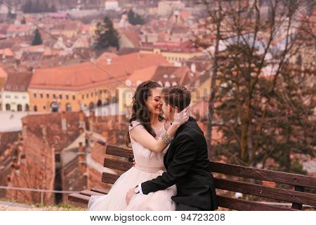 Bride And Groom Sitting On A Bench In The City