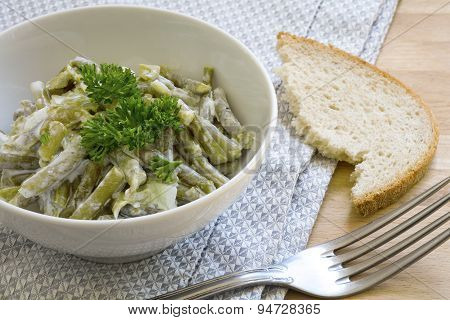Salad Of Green Beans With Sour Cream Dressing And Parsley Garnish In A White Bowl