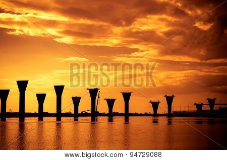 large concrete supports of the bridge under construction in the Gulf. Reflection in water. Port of S