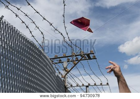 Man's Hand Throwing His Passport Folded As A Paper Airplane Over A Barbed Wire Fence