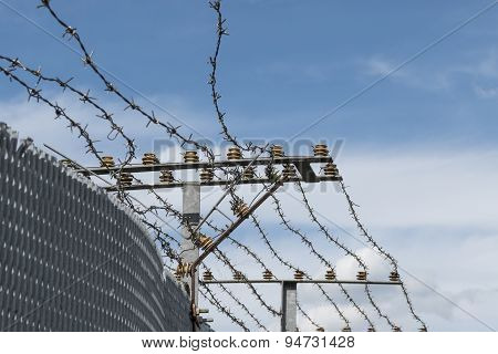 High Security Fence With Electric Barbed Wire Against A Blue Sky With Clouds, Copyspace