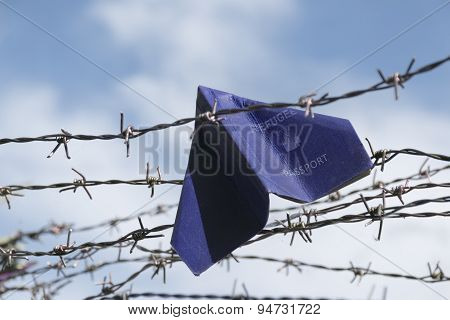 Refugee Labeled Passport Folded As A Paper Plane Hanging In A Barbed Wire