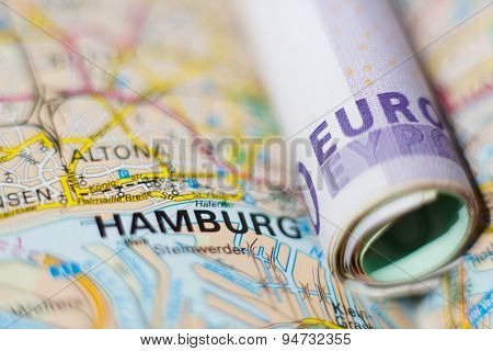 Euro Banknotes On A Geographical Map Of Hamburg