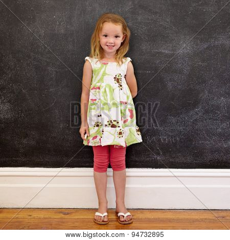 Beautiful Little Girl Standing Against Blackboard At Home