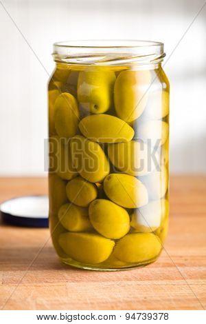pickled green olives in jar on kitchen table