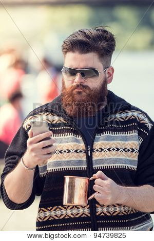 Trendy hipster young man with metal cup, using smart phone. Posing next to river