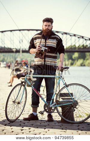 Trendy hipster young man with bicycle and vintage camera. Posing next to river
