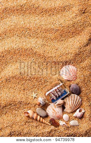 background of various shells and small ship in bottle on sand. Top view