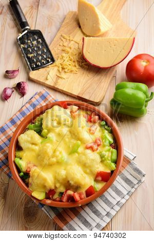 Vegetable gratin in a pot on a rustic table