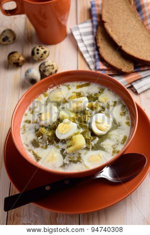 Sorrel soup with boiled quail eggs on a rustic table