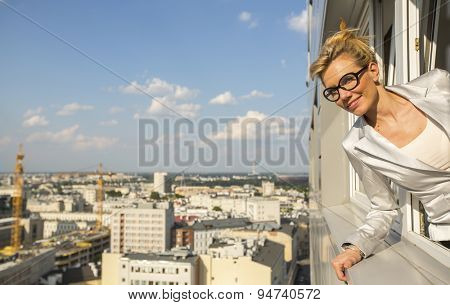 Young business woman looking from the window of new high-rise buildings.