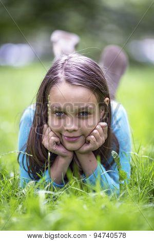 Portrait of cute little girl lying in green grass.