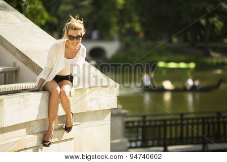 Beautiful young woman sitting in the Park near the lake.