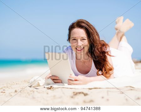 Woman in white clothes on the beach with tablet