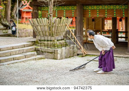 NARA, JAPAN - NOVEMBER 18, 2012: A Shinto Priest rakes a gravel Zen Garden at Kasuga-Taisha Shrine. The gardens have a long history in Japan and the surroundings are used to aid meditation.