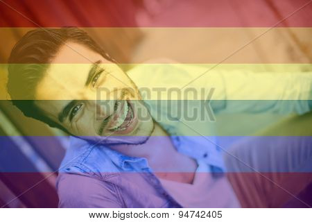 Celebrating marriage equality, handsome young man with the LGBT flag overlapped with medium opacity.