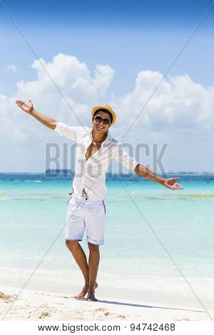Young man at the beach wearing casual clothing with his arms raised. Isla Mujeres, Cancun, Mexico.