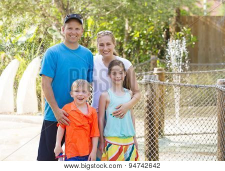Beautiful young family enjoying a day at an outdoors amusement park