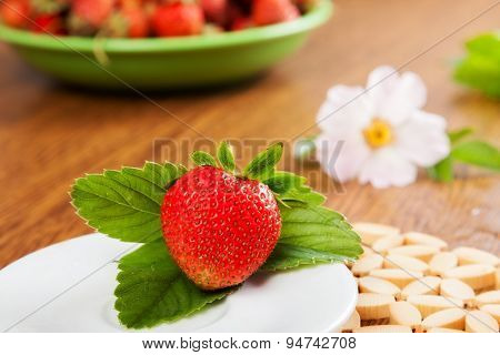 Beautiful juicy strawberry on leaves and on the saucer. With a flower on the background
