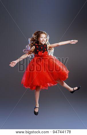 Cute teen girl in a beautiful festive dress dancing at studio. Beauty, children's fashion. Studio shot.