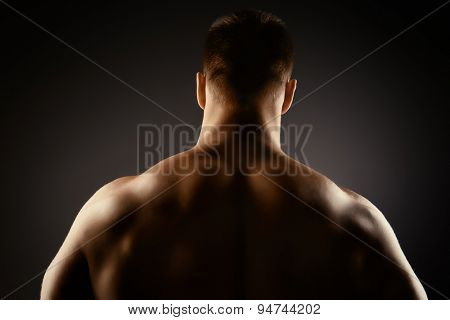 Athlete bodybuilder man demonstrating his perfect muscular body - muscles of the back and arms. Over black background.