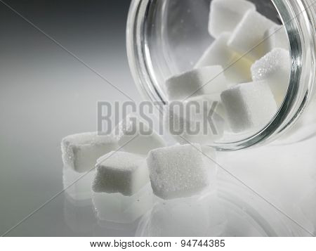 cube sugar pouring out from jar