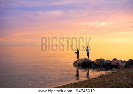Silhouette of two fishermen fishing in the sea at sunset
