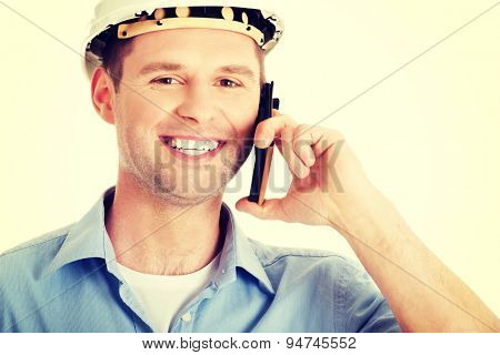 Contractor in hardhat smiles as he talks on his cell phone.
