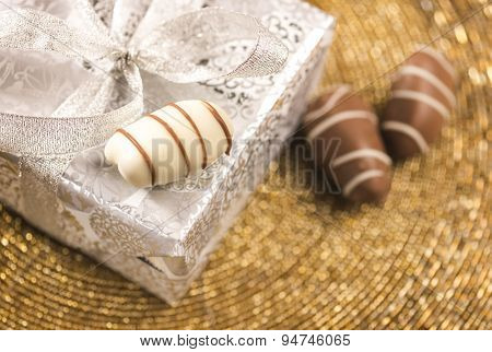 Close up of a gift pack wrapped in a silver paper along with three date-chocolates.