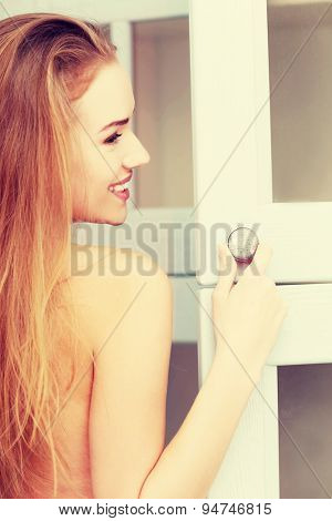 Young woman opening wardrobe doors