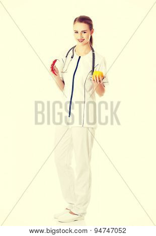 Female doctor in uniform holding pepper and chilli