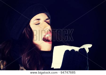 Beautiful young woman sneezing outside
