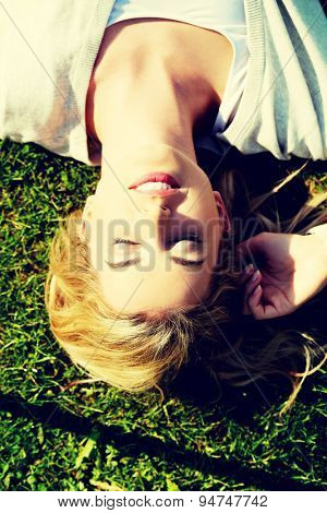 Young smiling woman lying on the grass