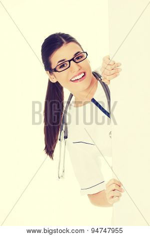 Happy doctor hiding behind a billboard