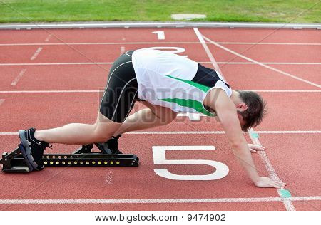 Athletic Man On The Starting Line Putting His Foot In The Starting Block