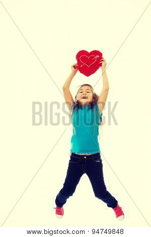 Young girl holding heart pillow