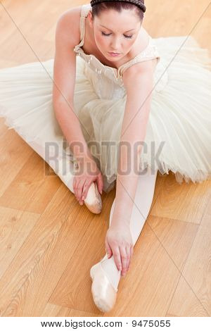 Radiant Ballerina Stretching On The Floor