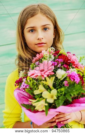 Beautiful girl with a bouquet of colorful flowers