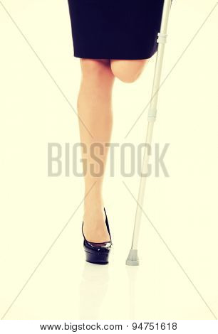 Businesswoman without a leg holding crutch