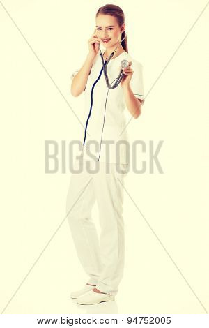 Female doctor in uniform examining by a stethoscope