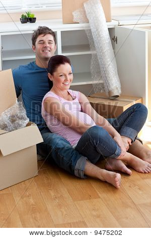 Joyful Young Future Parents Sitting On The Floor Surrounded By Cardboards