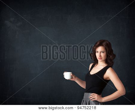 Businesswoman standing and holding a white cup on a black background