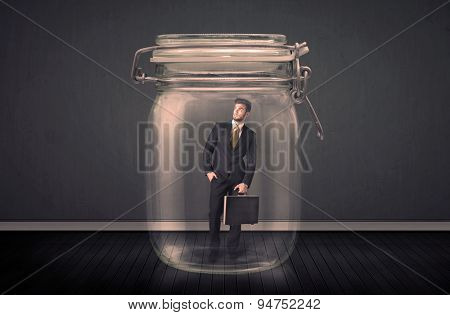 Businessman trapped into a glass jar concept on background
