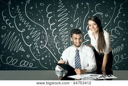 Business couple sitting at table with drawn curly lines and arrows on the background