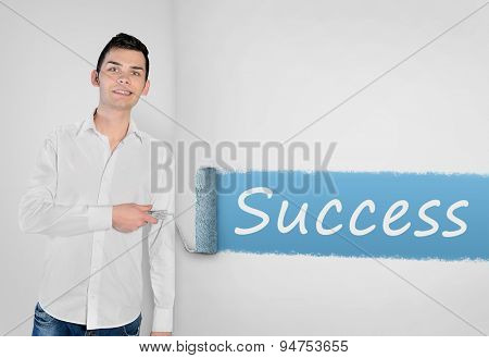Young man painting Success word on wall