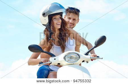 Beautiful young couple in love enjoying and having fun riding on a scooter in a beautiful nature