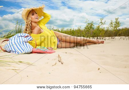 Smiling pretty blonde wearing sun hat at the beach
