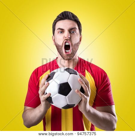 Fan on red and yellow uniform celebrates on yellow background