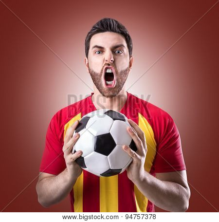 Fan on red and yellow uniform celebrates on red background