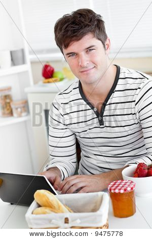 Young man Using His Laptop During His Breakfast Sitting In The Kitchen